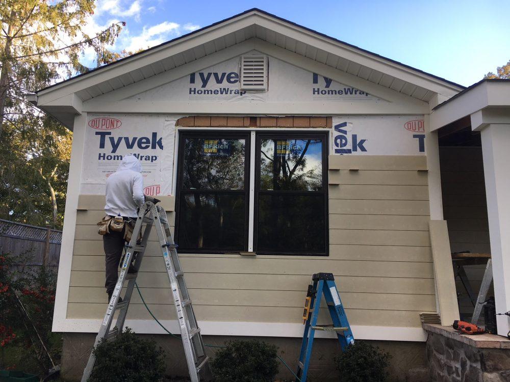 Crew member installing siding on house
