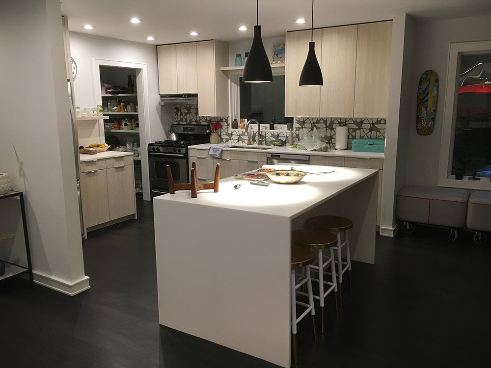 Smaller kitchen beautifully renovated with black wooden flooring and beige cabinets