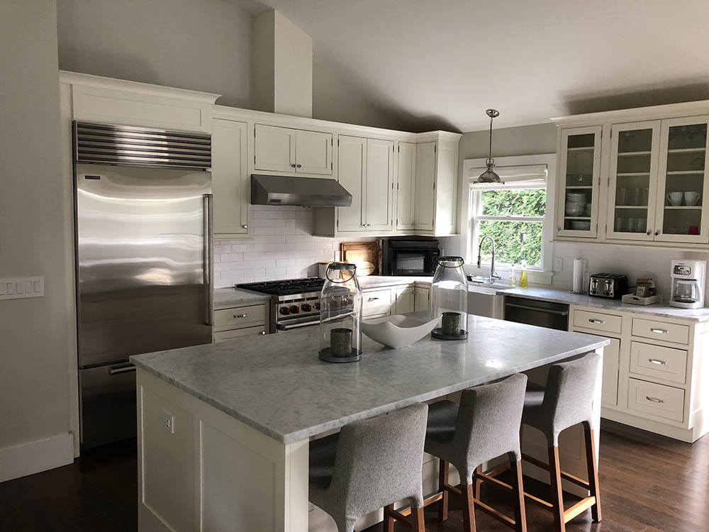 This renovated kitchen in the Hamptons was given a dark hardwood floor and white cabinets