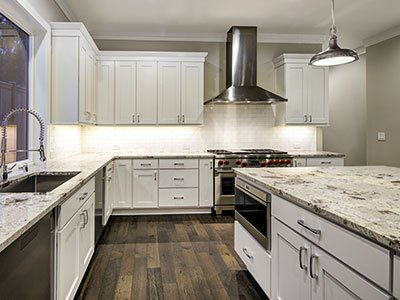 Average-sized kitchen with white cabinets, silver finish appliances, large island with quartz countertop, and dark wooden floor.