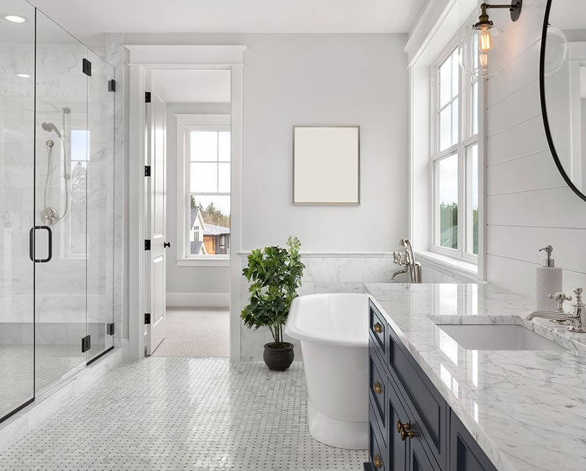 Modern bathroom with white marble, black cabinets, walk-in shower, and large windows
