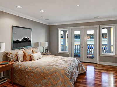 Bedroom with gray painted walls, large bed, wooden floor, and white windows.
