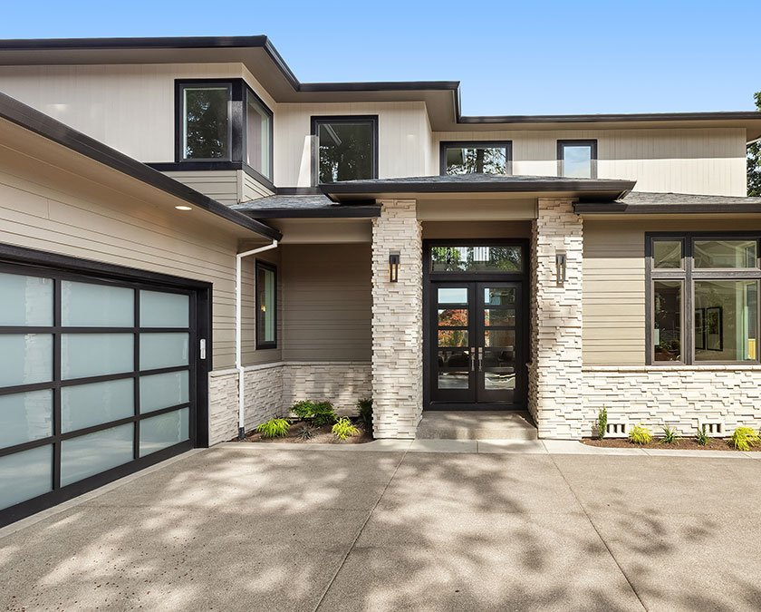 Exterior house view with stone decor walls, glass door garage, dark windows and door, and large alley.