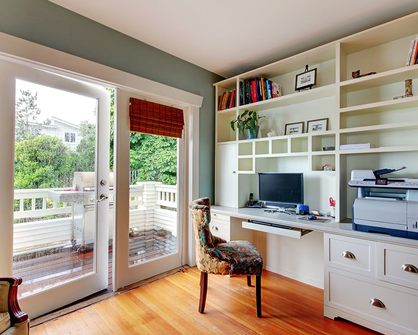 Home office with wooden floor, greenish walls, white furniture, and large windows.