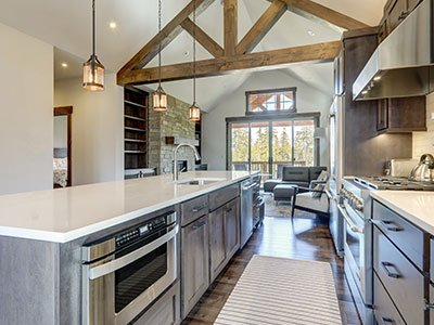 Large kitchen with gray cabinets, large island with quartz countertop, silver finish appliances, laminate floor, and beige carpet.