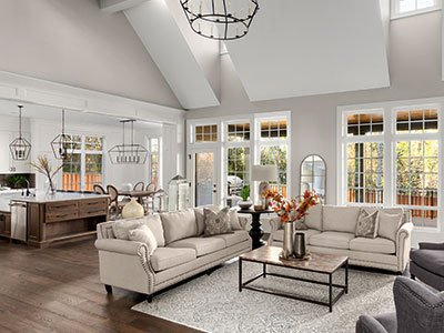 Large living room with wooden floor, white carpet, beige couches, gray armchairs, open space kitchen, large windows, and chandelier.