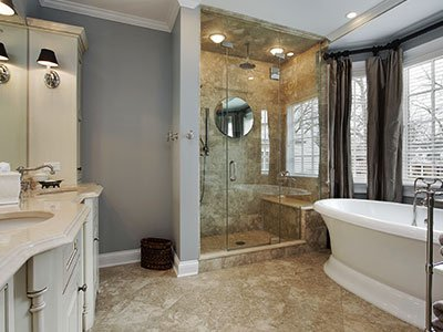 Large bathroom with gray walls, tiled floor, white cabinets, glass door shower, and a white tub.