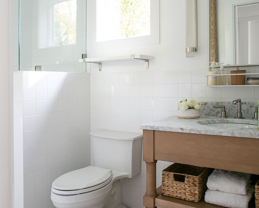 Medium bathroom with white walls and wood cabinets