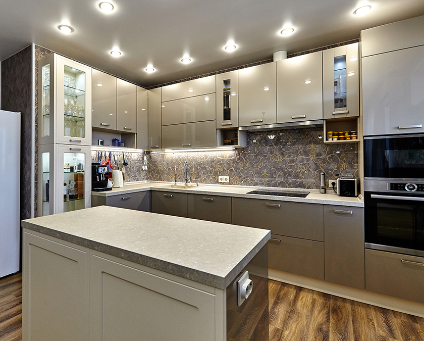 Modern kitchen with shiny beige cabinets, island with quartz countertop, wooden floor, decorated backsplash, and silver finish appliances.
