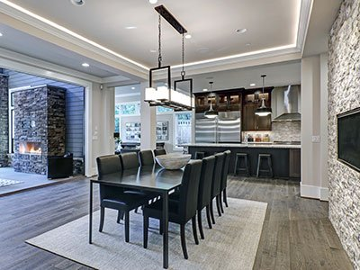 Open space dining area with dark table, black leather chairs, stone decor on the wall, wooden floor, large glass door leading to patio outside, and open space kitchen view in the background.