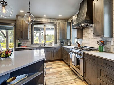 Small kitchen with brown cabinets, laminate floor, gray island with quartz countertop, and warm lighting.